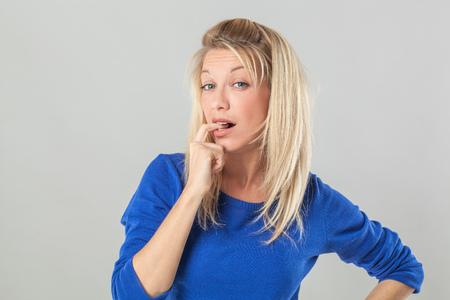 dudando: joven atractiva sonriente mujer vacila rubia, que muerde su dedo para la duda y la pregunta con la imaginación, fondo gris, cubierta Foto de archivo