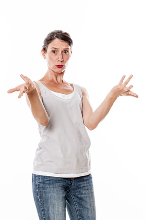 unhappy young woman with tied hair standing, expressing her anxiety and doubt with her hands, isolated, white background Stock Photo