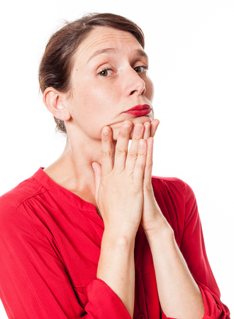 disinterest: portrait of a thinking young woman holding her chin with her hands, expressing disinterest and boredom, isolated, white background