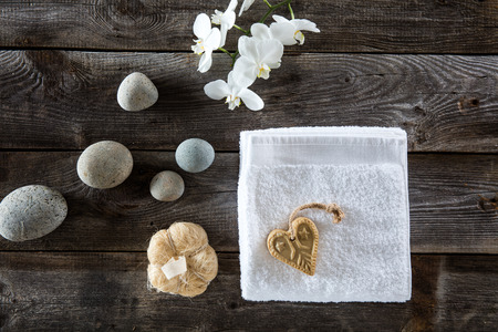 mimos: minimal pampering concept with flat lay still life of beautiful pebbles, loofah, white towel and orchids and heart-shaped traditional soap for symbol of zen dry brushing on rustic old wood background