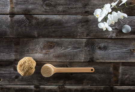 rustic old wood background with back brush, natural sponge and white orchids for symbol of wellbeing and femininity for beauty concept, flat lay with copy space