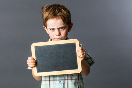 conflicting: annoyed young child showing a copy space writing slate to express an unhappy statement or his conflicting attitude in learning at preschool, grey background indoors