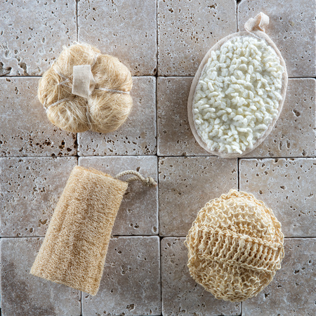 stone wash: body care accessories with loofah and cotton sponges to wash up and detox set over minimal stone background, flat lay
