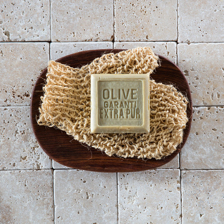 mitt: top view of an organic olive oil soap on stimulating mitt set in beautiful dark wooden bowl on stone background for cleansing concept and spa wallpaper