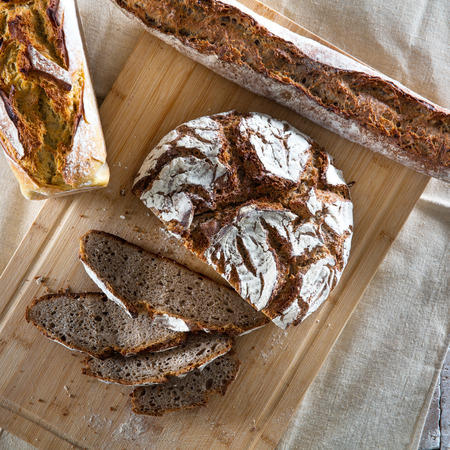 healthy organic whole wheat breads still-life with a round loaf, a French baguette and a molded crusted bread set on a wooden board on beige fabric, top view in flat lay Фото со стока