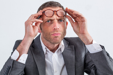 skeptical: skeptical middle aged businessman with eyeglasses on his forehead frowning for suspicion, reproach or doubt, white background, indoor Stock Photo