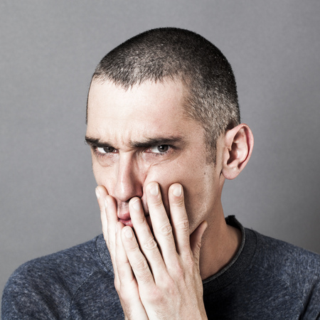 disturbed: disturbed unhappy 30s man having doubts, putting his hands on his cheeks, pouting his mouth for suspicion and doubt, grey background indoor Stock Photo