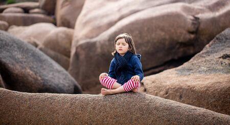 onerelaxing de 5 años de edad del niño con los ojos cerrados sentado en un paisaje de piedra de granito, la meditación y la respiración por sí solo al aire libre, en busca de la concentración de yoga, la primavera