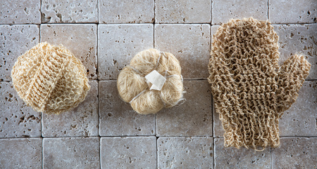 mitt: dry brushing and exfoliation with a set of natural loofah sponges and stimulating mitt for body massage over pure limestone background, top view Stock Photo