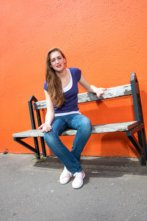 complaining: unhappy young woman sitting on a bench, complaining, expressing annoyance or concern over an orange wall in the street, sunny outdoors Stock Photo
