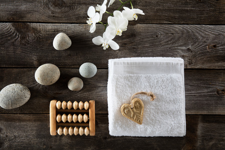 massager: flat lay for valentines day concept with heart-shaped soap, pure white towel and flowers, beautiful pebbles and foot care massage over old wood background