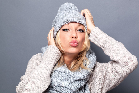 pouting: love and happiness concept - fashionable blond girl wearing gray winter hat and scarf pouting for valentines, grey background studio Stock Photo