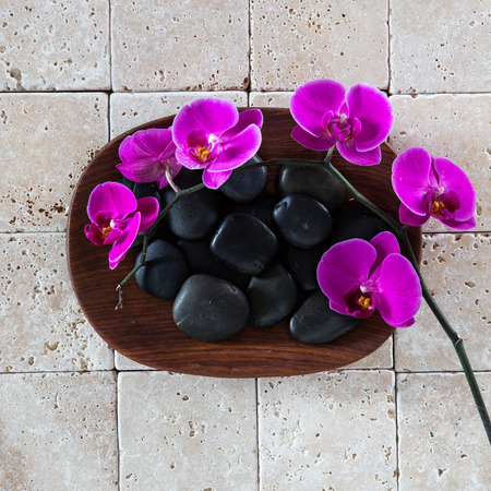wellness spa concept with black massage pebbles and pink orchids over wood and pure limestone background for zen wallpaper, flat lay Stock Photo