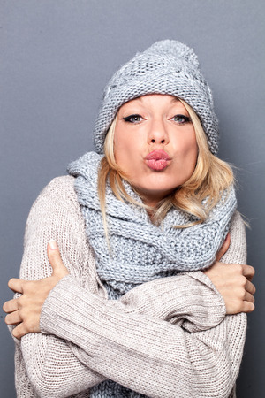 pouting: pouting sophisticated beautiful young blond woman feeling warm and sexy wearing grey winter hat and scarf for valentines day, studio shot