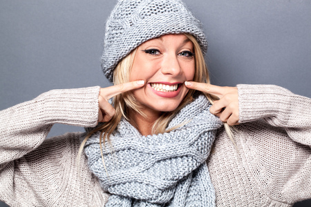 fake smile: cheerful young sophisticated blond woman playing with a fake smile for a sexy warm winter, grey background