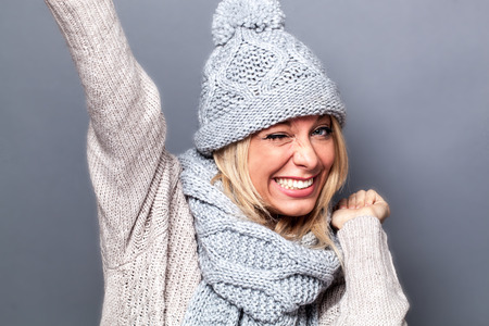 success and seduction concept - flirting young woman winking for cool and victorious attitude in winter, grey background