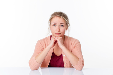 elbows: unhappy young blond woman sitting with her elbows on a white empty office desk, apologizing and feeling sorry, white background, indoor