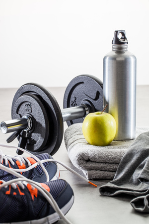 wellness and gym concepts, to work out with dumbbells, aluminium bottle and a healthy apple set on a grey towel Stock Photo