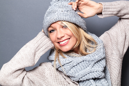 happy beautiful blond girl smiling with a fashionable sexy winter hat, enjoying comfortable temperatures and wellness, grey background
