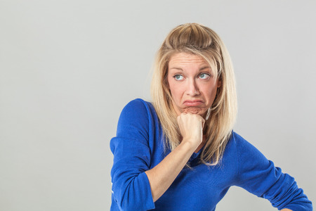 unhappiness: bored young blond woman looking up, expressing disappointment and unhappiness, pouting and holding her chin for regret, grey background, indoor