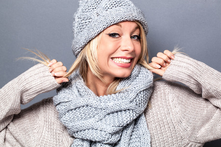 fake smile: girly sophisticated young blond woman playing with her hair and a fake smile for an exciting warm winter, gray background