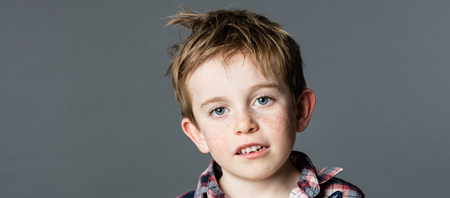 mischievous: adorable mischievous young kid with freckles and messy red hair smiling for wellbeing and childhood, grey background, closeup portrait Stock Photo