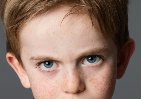 closeup of a displeased young boy with big blue eyes and freckles for attitude and childhood anger, grey background Stock Photo