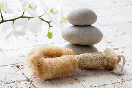mimos: cuidado del cuerpo y la meditación concepto con el cepillo para el cuerpo esponja natural y el equilibrio de las piedras para el símbolo de paz, copia espacio sobre las flores de color blanco puro