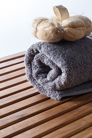 mitt: closeup of loofah mitt for purifying body care on rolled up grey cotton towel for pure exfoliation and hygiene, copy space Stock Photo