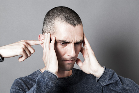psychiatry: concept of headache, tinnitus, bipolar behavior or male psychiatry with young man in pain touching his head for additional closed ears, grey background