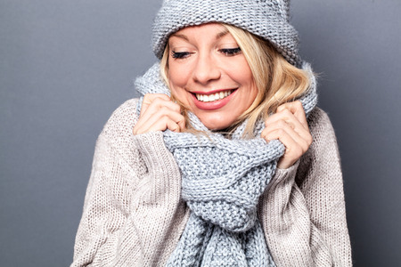 comfy: comfy young beautiful blond woman smiling with a fashionable sexy winter scarf, enjoying comfort and wellbeing, grey background Stock Photo