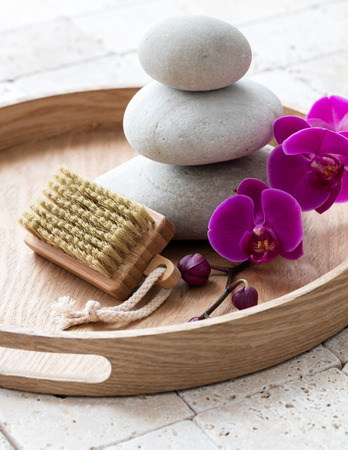 inner beauty: concept of inner beauty and nail care with wooden brush, relaxing stack of stones over pink orchid flowers and symbol of mineral bath