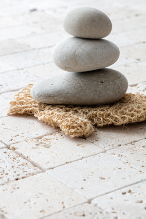 inner beauty: concept of purity, inner beauty and massage with stack of balancing stones or pebbles with natural loofah mitt over feng shui limestone background