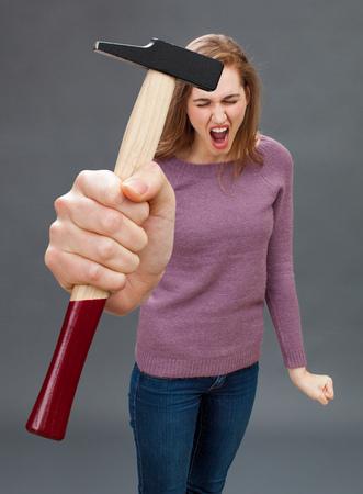 trabajo manual: enfurecido joven y bella mujer gritando con un martillo en la mano simbólica para expresar su frustración al bricolaje, mejoras para el hogar o la reparación herramienta de trabajo hecho a mano