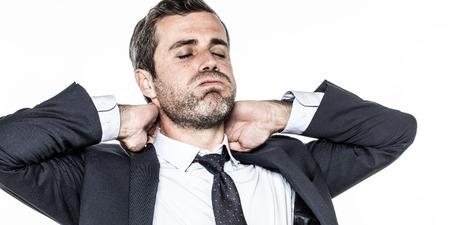 exhaustion: tired young bearded businessman with cheeks puffed, relaxing his tensed neck against corporate exhaustion, isolated over white background