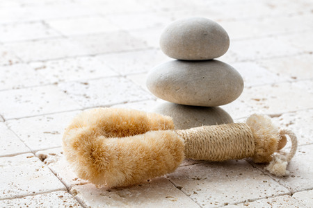 inner beauty: dry brushing and mindfulness concept with natural loofah body brush and balancing stones for symbol of peace, copy space over clean limestone Stock Photo