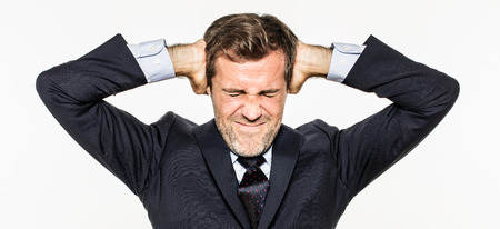 annoyed young business man covering his ears from corporate burnout at work, suffering from noise at work, having a breakdown, isolated, white background