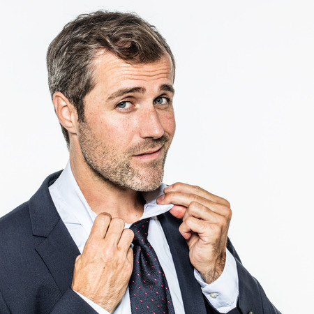 sexy bearded businessman checking, fixing or opening his collar and necktie for elegance and sophistication at work, isolated, copy space over white background