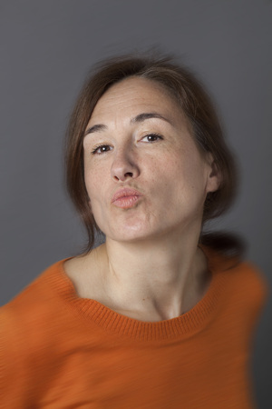 fun beautiful middle aged woman pouting for seduction, love and happiness, wearing an orange sweater over grey background Stock Photo