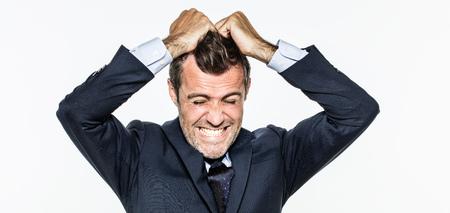 joven hombre de negocios enfurecido tirando de su pelo hacia fuera para exasperación, que tiene una quemadura en el trabajo, gritando por la frustración y el estrés, aislado, fondo blanco Foto de archivo