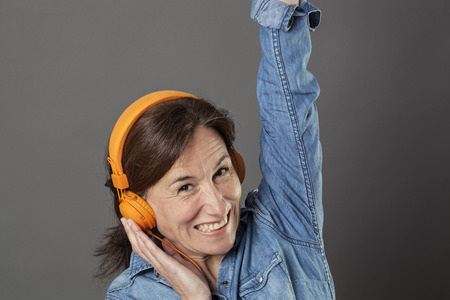 joyous: fun middle aged woman listening to music on orange headphones, raising her arms for happiness and joyous wellbeing, grey background