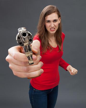 venganza: furiosa mujer joven de autodefensa con una pistola de mano de gran tamaño en el primer plano, que expresa la venganza, el odio o la acusación con un arma de fuego