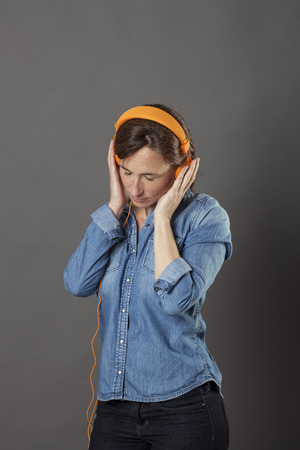 eyes looking down: relaxing middle aged woman standing with eyes closed, listening to zen music on orange headphones, enjoying peace and wellness, grey background
