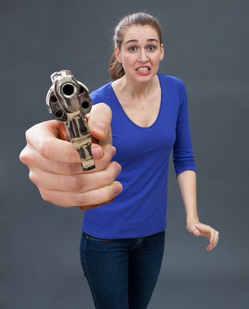 scared beautiful young woman holding an oversized hand gun in the foreground, expressing anxiety and surprise for firearm self-defense