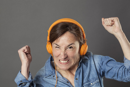 enraged: angry middle aged woman frowning with enraged arms raised in listening to noise or music on fashionable headphones on, grey background