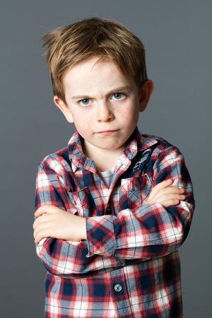 conflicted young 6-year old kid with messy red hair standing, crossing his arms to express his disagreement and frustration, grey background