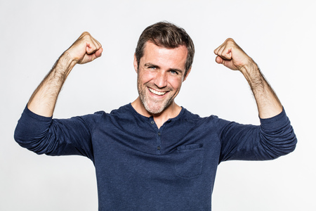 goodlooking: good-looking young bearded man smiling with fists up, showing his wellbeing and success with happiness and energy, isolated, white background Stock Photo