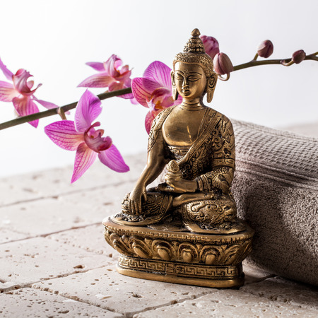 Bronze Buddha over towel and flowers for concept of spirituality and feng shui over limestone background