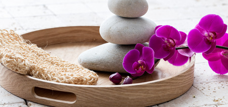 concept of massage and exfoliation with natural loofah mitt, relaxing stack of stones over pink orchid flowers and symbol of pampering bath