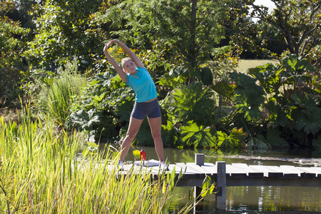 healthy sport: fitness beautiful girl with summer sport shorts stretching her arms and exercising for healthy sport on a wooden bridge and water in a beautiful green park